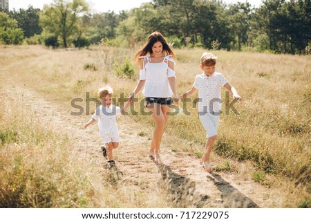 Mother with two sons running trough the field at sunny beautiful day. Boys are redheaded. 2 years and 7 years old.