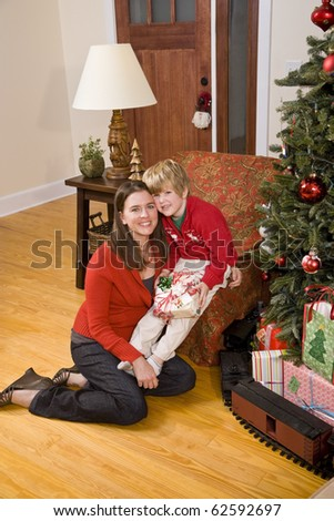 Mother with 4 year old boy holding present by Christmas tree - stock photo