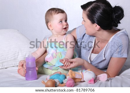 Mother with young baby and bottle on bed - stock photo