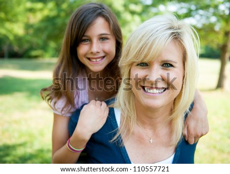 Mother with young daughter on her back smiling - stock photo