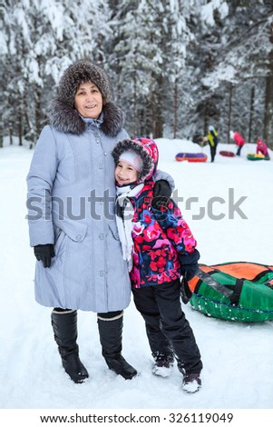 Mother with young daughter standing in wintry forest, walking with snow tube - stock photo