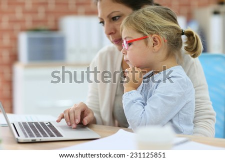 Mother working at home-office with daughter on her lap - stock photo