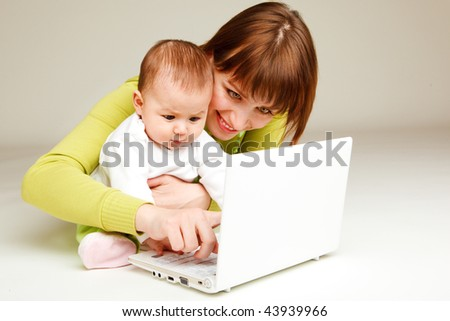 Mother working at the laptop, baby beside her - stock photo