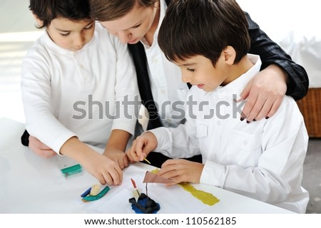 Mother working with sons on homework project - stock photo