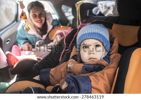 Mother worried about her children's safety in a car Son and daughter near to mom Babes sitting inside modern auto People look at camera The idea of safe traffic - stock photo