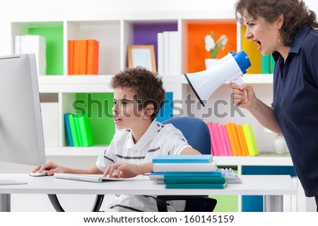 mother yelling at his son, boy play computer games - stock photo