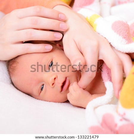 mothercare, cute newborn baby with young mother's hands - stock photo