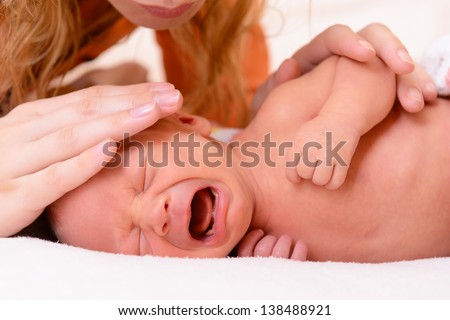 mothercare, young mother calms her newborn baby during she is crying and screaming - stock photo