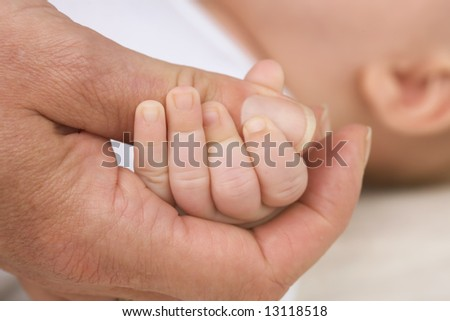 motherhand and little baby fingers - stock photo