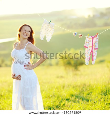 motherhood, beautiful young pregnant woman in decorated garden - stock photo