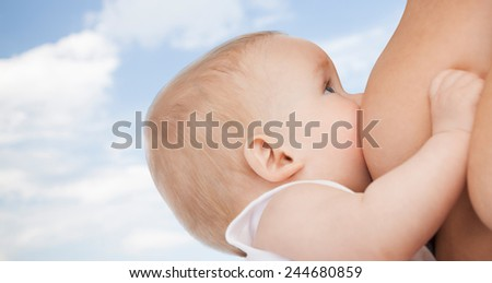 motherhood, children, people and care concept - close up of mother breast feeding adorable baby over blue sky background - stock photo