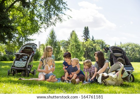 Mothers and children enjoying picnic in summer park - stock photo