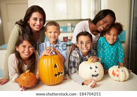 Mothers And Children Making Halloween Lanterns - stock photo