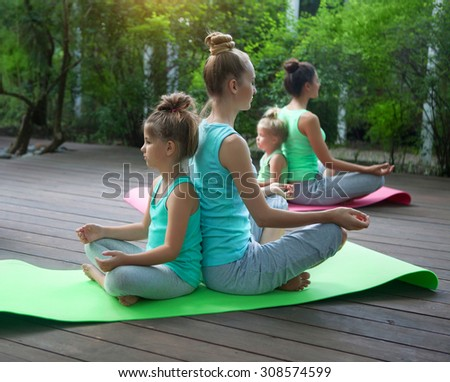 Mothers and daughters doing exercise practicing yoga outdoors. Healthy lifestyle - stock photo
