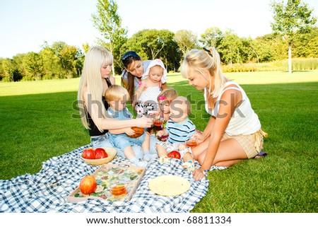 Mothers and kids having picnic in the backyard - stock photo