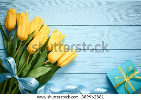Mothers Day background. Tulips bouquet and gift box on blue wood. Beautiful spring pink and yellow flowers. Still life, top view, copy space. Unusual creative holiday greeting card  - stock photo