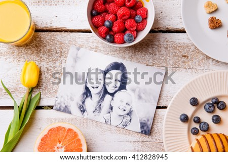 Mothers day composition. Black-and-white picture of mother with her daughters and a breakfast meal. Studio shot on wooden background. - stock photo