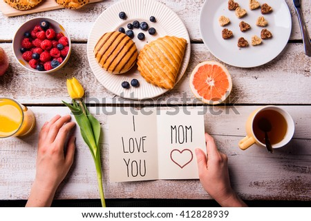 Mothers day composition. Hands of unrecognizable woman holding greeting card with I love you, Mom, text. Breakfast meal. Studio shot on wooden background. - stock photo