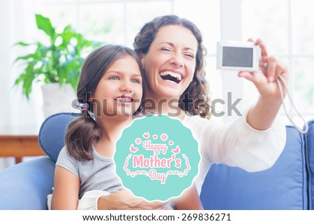 mothers day greeting against happy mother and daughter sitting on the couch and taking selfie - stock photo