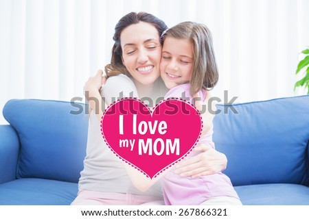 mothers day greeting against mother and daughter hugging on couch - stock photo