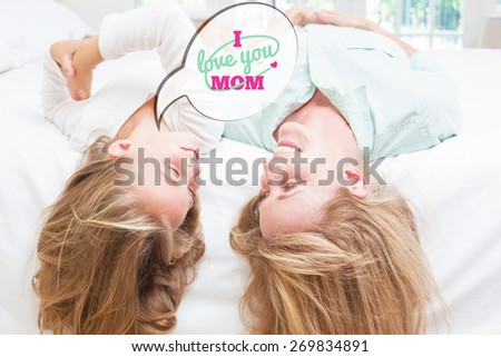 mothers day greeting against mother and daughter lying on the bed - stock photo