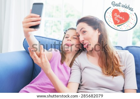 mothers day greeting against mother and daughter taking a selfie - stock photo