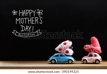 Mothers Day message with pink and blue cars carrying heart cushions - stock photo