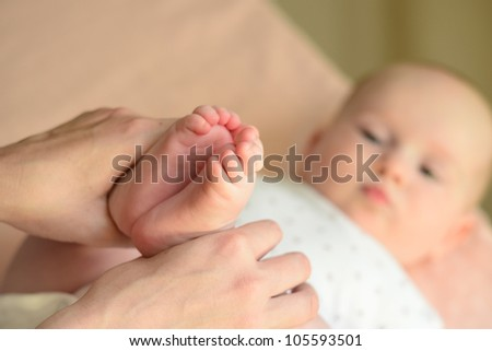 mothers hand holding babies little feet