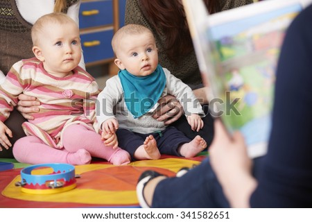 Mothers With Children At Baby Group Listening To Story - stock photo