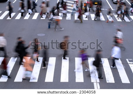 Motion blur aspect of people crossing the street in a big city. - stock photo