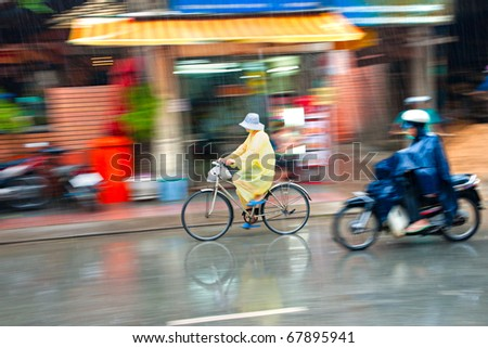 Motion blur astract of a bike and a motorbike rider in Ho Chi Minh City, Vietnam. - stock photo