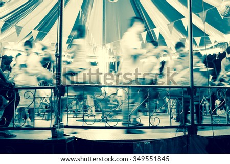Motion blur children playing carousel horses - black and white effect - stock photo