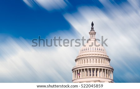 Motion blur clouds illustrating time moving quickly past  dome of Capitol senate building in Washington DC