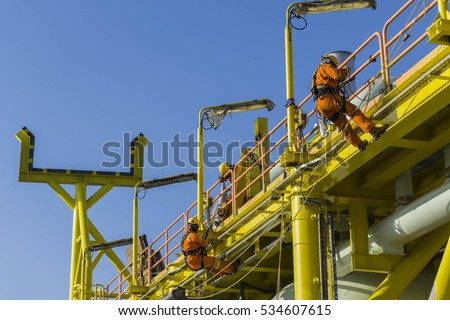 Motion blur effect. Man working at height. Abseilers climbing and hanging at the edge of oil and gas platform in the middle of sea.