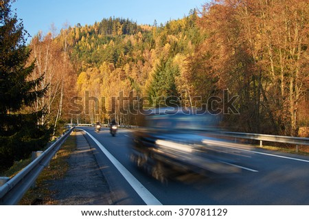 Motion blur fast moving passenger car and motorcycles on asphalt road in a valley between forested mountains in autumn colors. Sunny autumn day with blue sky.