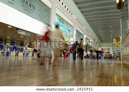 Motion blur image of people at barcelona airport - stock photo