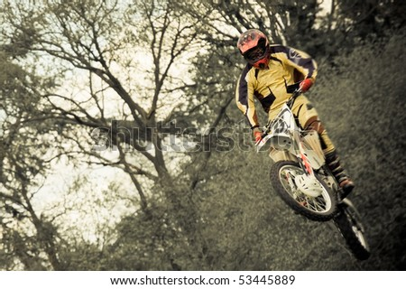 motion blur motocross rider in mid-air - stock photo