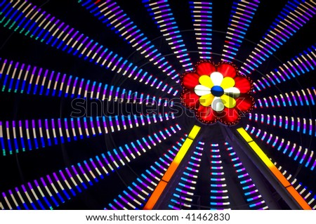 motion blur of a colorful ferris wheel at night - stock photo