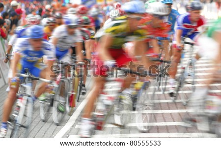 Motion blur of a group of cyclists in action during a cycling tour. - stock photo