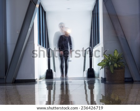 motion blur of a man walking on escalator, move up - stock photo