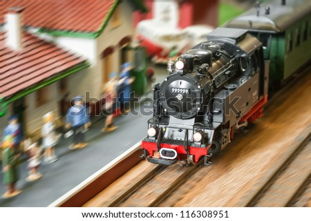 motion blur of a model railroad steam locomotive (with fake number) speeding through a station - stock photo