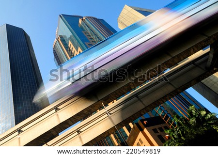 Motion blur of a skytrain speeding through a modern business district.  - stock photo