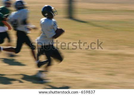 motion blur of boy running in for the touchdown - stock photo