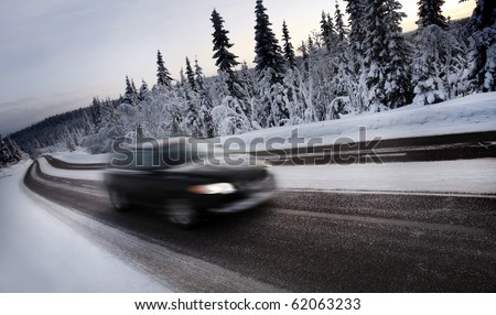 Motion Blur of Car Driving Down Snow Covered Road - stock photo