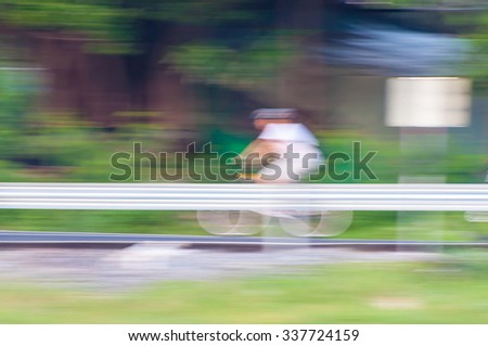 Motion blur of cyclist riding a bike on a bicycle path - stock photo