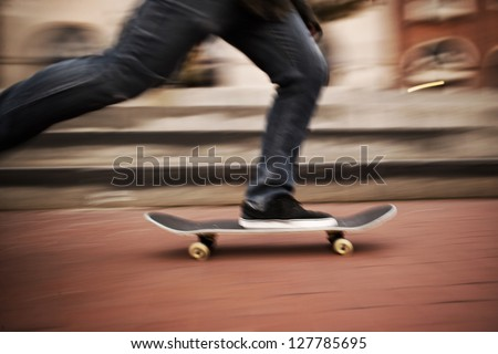 Motion blur of fast skateboarder feet moving - stock photo