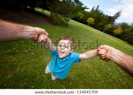Motion blur of father holding onto son's arm while spinning. Sharp focus on eyes - stock photo