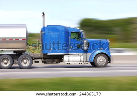 Motion blur of fuel tanker on highway. - stock photo