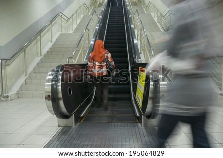 Motion blur of people on escalator - stock photo