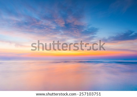 Motion blur of the sea under vivid twilight sunset sky with long exposure effect. - stock photo